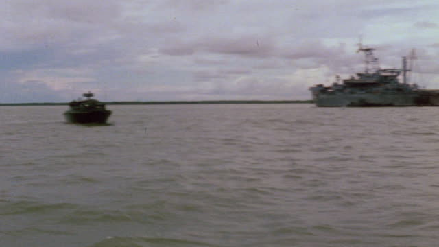 Harnett County and river patrol boats in Mekong Delta and crew member in stern of PBR / Vietnam