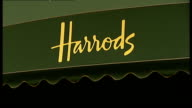 London EXT Awning over department store window with 'Harrods' logo / People alon g outside Harrods / Upper stories of Harrods store / More of...
