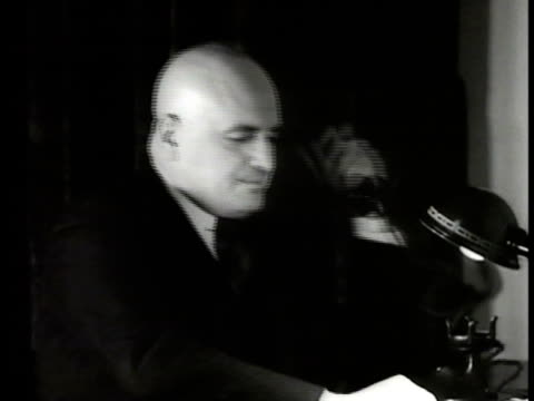 Harry J Anslinger sitting at desk w/ Herald Graves sitting FG talking on telephone saying 'great work' talking w/ Graves about smugglers trying to...