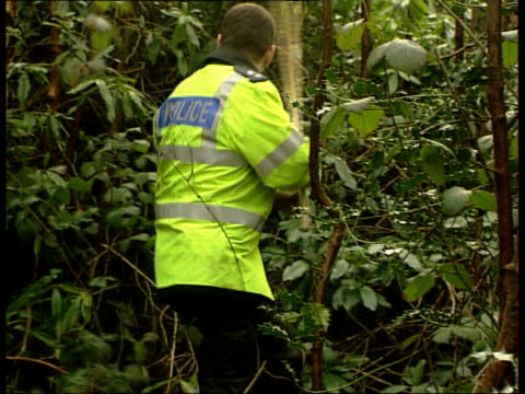 LIB ENGLAND Hastings St Leonards BV Policeman searching undergrowth TGV Police along searching river