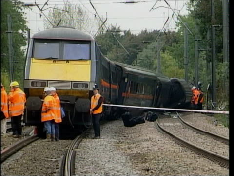 Corporate manslaughter threat LIB ENGLAND Hertfordshire Hatfield EXT Accident investigators standing next derailed train as examining wheels lying on...