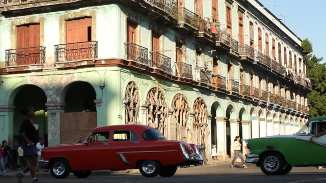 WS, havana building w/ Vintage American cars driving by, Cuba