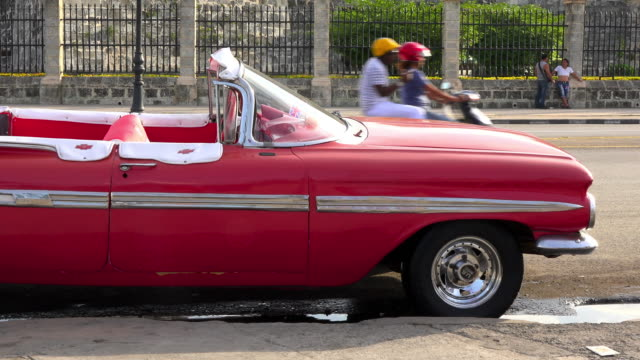 Havana, Cuba: panning from and old convertible American car which works as a tourist taxi in the 'malecon' towards the everyday lifestyle in the area