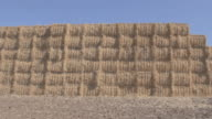 Hay stacks pilled up in field linear angle