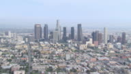 AERIAL Hazy Los Angeles skyline with office buildings and skyscrapers / California, United States