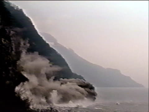 Hazy pixilated shot of violent landslide displaces thousands of tons of rock and dirt into the sea