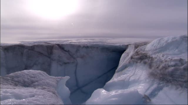 A hazy sun shines above a glacier. Available in HD.