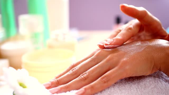 HD1080:Applying skin moisturizer onto hands.