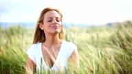 HD1080:Blond woman enjoying mild summer breeze outdoors.