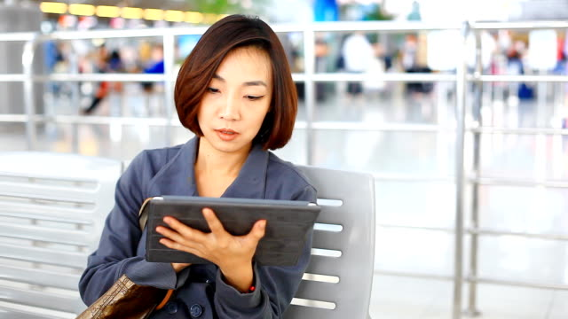 HD:Asian cute women play tablet at the airport.