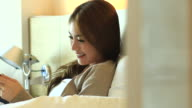 HD:Asian cute women play tablet on the bed.