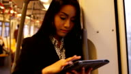 HD:Asian cute women play tablet on the train.