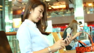 HD:Asian woman using mobile phone at the airport.