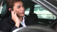 HD:Asian young businessman driving talking on mobile phone.