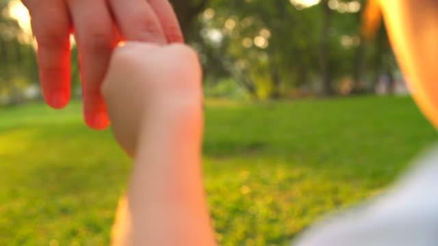 HD-bambino tenendo il dito della madre nel parco.