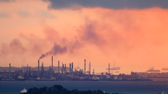 HD:Black smoke pollution from industrial area silhouette at sunset.
