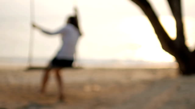 HD:Blurred Woman on swing on the beach with sea at sunset time , slow motion , relaxation concept
