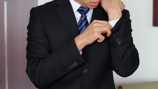 HD:Businessman adjusting suit and tie.