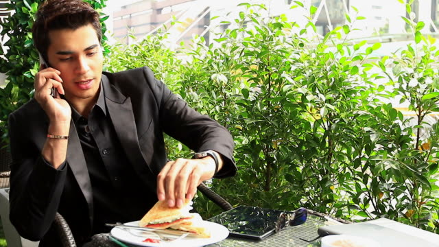 HD:Businessman talking on mobile phone during meal outdoors
