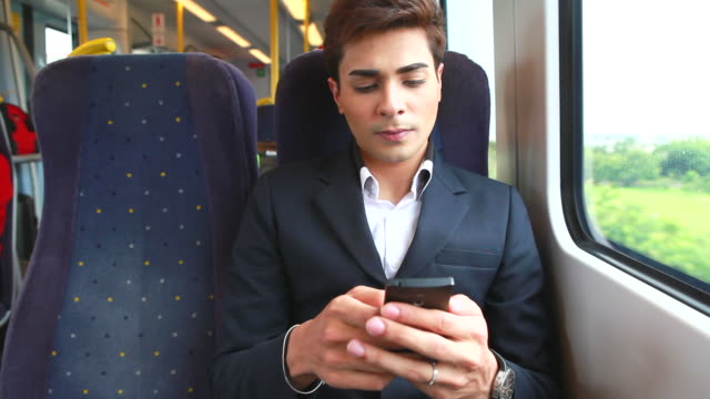 HD:Businessman using mobile phone on train