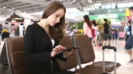 HD:Businesswoman playing with tablet while waiting for her flight.