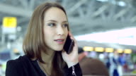 HD:Businesswoman talking by using mobile phone at airport.