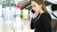 HD:Businesswoman talking with mobile phone while waiting for her flight.
