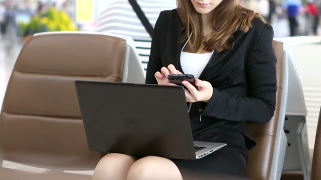HD:Businesswoman working by using mobile phone at airport..