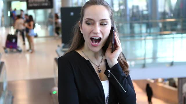 HD:businesswoman fungerar genom att använda mobiltelefon på flygplats.