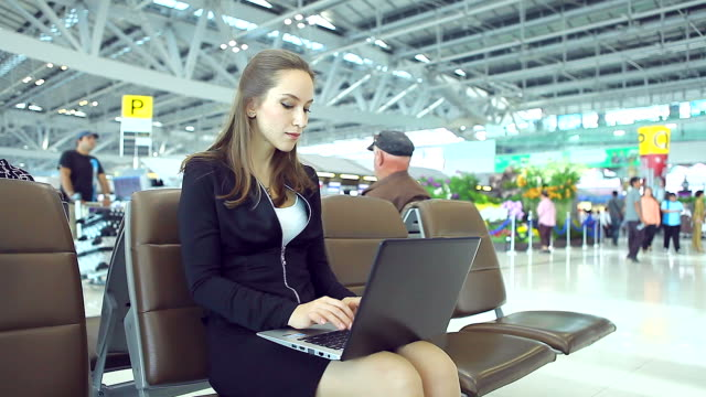 HD:Businesswoman working by using notebook at airport.