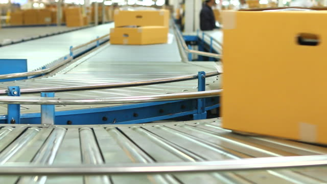 HD:Carton box moving on conveyor rollers.