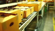 HD:Carton box moving on conveyor rollers.