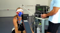 HD:female Athlete Doing ECG and VO2 test on Rowing Machine