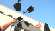 HD:Graduates throwing graduation hats in the air.