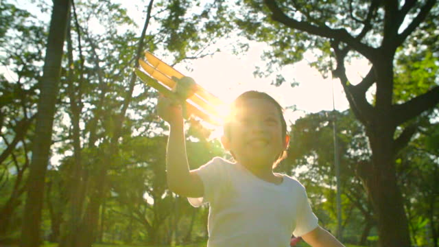 HD:Happy child playing wooden airplane in the park(Slow motion)..