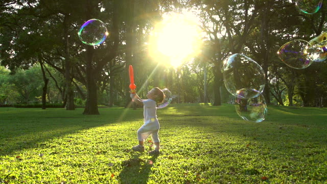 HD:Little boy in the sunset catches soap bubbles.