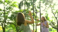 HD:Little girl and her mom play bubbles at park.