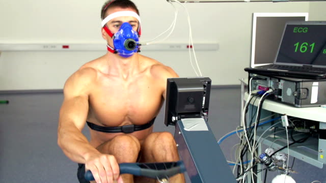 HD:Male Athlete Performing ECG and VO2 test on Rowing Simulator