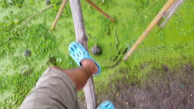 HD:Man walking cross river on bamboo bridge.