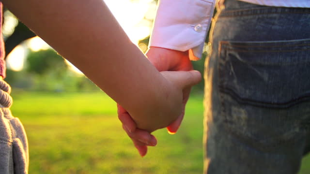 HD:Mother and daughter holding hands together in summer day outdoors