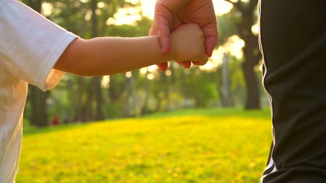 HD:Mother hålla hand av hans son promenader i parken.