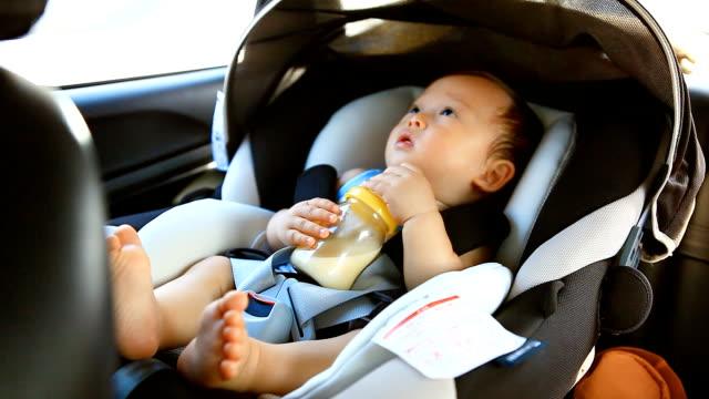 HD:Portrait of a little boy drinking milk in the car.