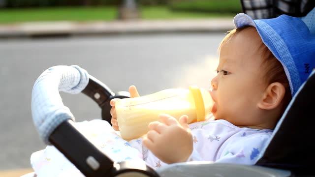 HD:Portrait of a little boy drinking milk in the park.