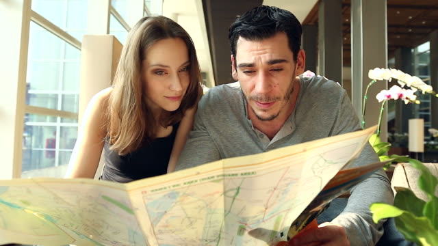 HD:Portrait of tourist couple checking city map at lobby hotel.