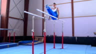 HD:Shot of Male Gymnast Performing Routine on Parallel Bars