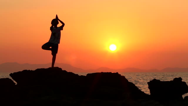 HD:Silhouette of young girl exercise YOGA.
