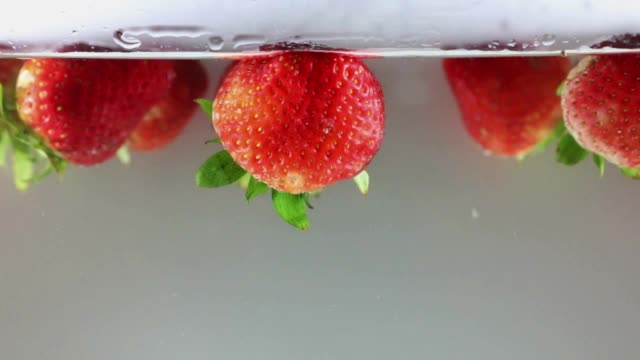 HD:slow motion ,strawberries drop in to water on white  background , slow motion