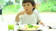 HD:Toddler in white shirt eating breakfast.