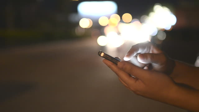 HD:Woman touching smartphone at night time