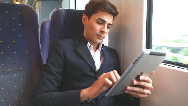 HD:Young businessman play tablet on the train.